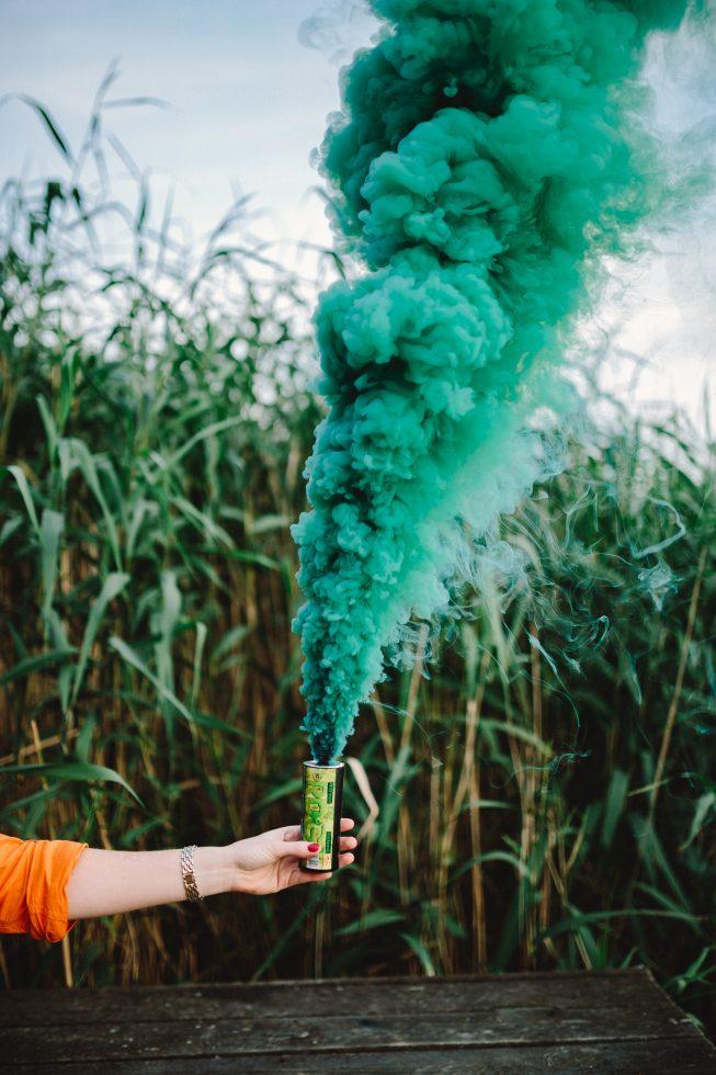 kaboompics.com_Green smoke bomb in female hand